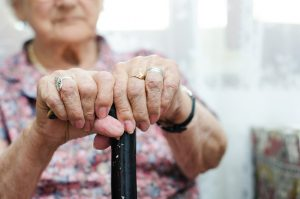 Two hand of senior woman sitting in chair holding walking stick